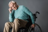 upset retired man sitting in wheelchair and looking at camera on grey
