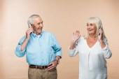 glückliches Rentnerehepaar mit grauen Haaren, Smartphone isoliert auf beige