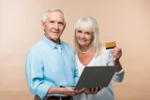 happy retired woman holding credit card near senior husband with laptop isolated on beige