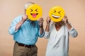 KYIV, UKRAINE - JUNE 14, 2019: retired couple covering faces with yellow happy smileys isolated on beige