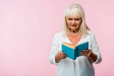 senior woman with grey hair reading book isolated on pink