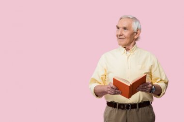 happy retired man holding book and smiling isolated on pink