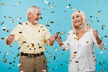 happy retired husband and wife near  falling confetti on blue