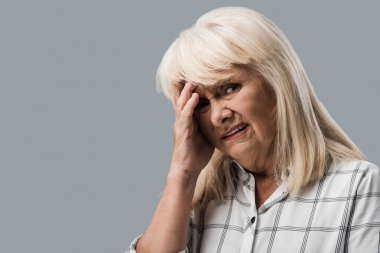 Tired and upset retired woman touching head and looking at camera isolated on grey stock vector