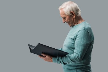 happy retired man with grey hair looking at photo album isolated on grey