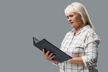 upset retired woman looking at photo album isolated on grey