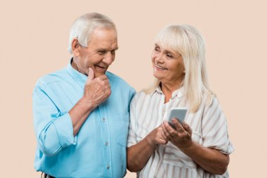 cheerful retired woman holding smartphone and looking at husband isolated on beige