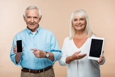 Happy retired man and wife pointing with finger at smartphone and digital tablet with blank screens isolated on beige stock vector