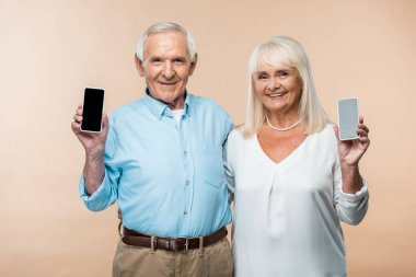 happy retired couple with grey hair holding smartphones with blank screen isolated on beige
