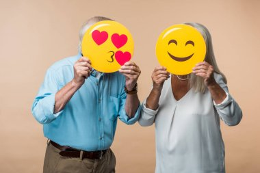 KYIV, UKRAINE - JUNE 14, 2019: senior couple covering faces with yellow smileys isolated on beige stock vector