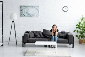 depressed young woman sitting on sofa in spacious room and holding hands near head