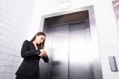 fiatal üzletasszony hivatalos kopás ellenőrzési időt néz várva a lift