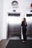 a lobbyban álló, formális kopást nyújtó üzletasszony hátnézete és liftre várva