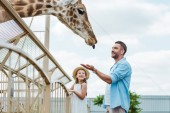 selective focus of cheerful man gesturing while looking at giraffe near kid in zoo
