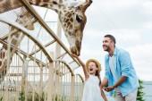 Fotografie Selektiver Fokus von fröhlichem Mann und Kind mit geschlossenen Augen beim Füttern von Giraffen im Zoo
