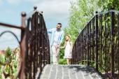 selektivní zaměření otce přidržením se dcery při chůzi po mostě