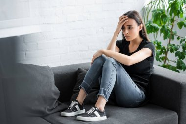 pretty young woman suffering from depression while sitting on couch at home and holding hand near head