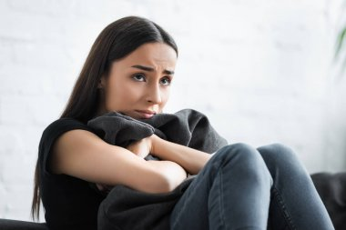 depressed young woman hugging pillow and looking away while sitting on sofa at home