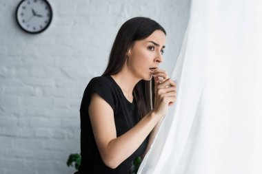 frightened girl looking out window while suffering from panic attack at home