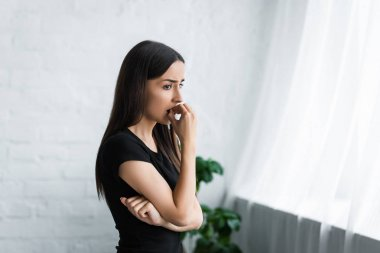 upset young woman looking away while suffering from depression at home