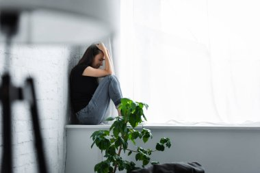 Selective focus of depressed young woman crying while sitting on window sill and holding hands on head stock vector
