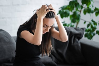frustrated young woman suffering from depression while sitting on couch and holding hands on head