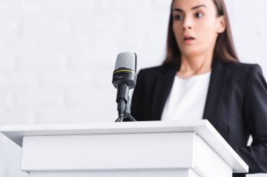 selective focus of scared young lecturer, suffering from fear of public speaking, standing near microphone on podium tribune