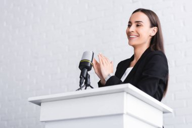 happy speaker clapping hands while standing on podium tribune in conference hall