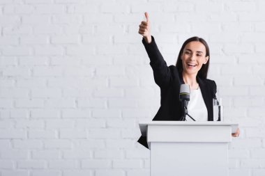 happy, attractive lecturer showing thumb up while standing on podium tribune