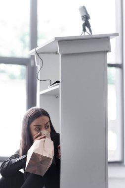 frightened lecturer breathing into paper bag while sitting on floor in conference hall and suffering from panic attack