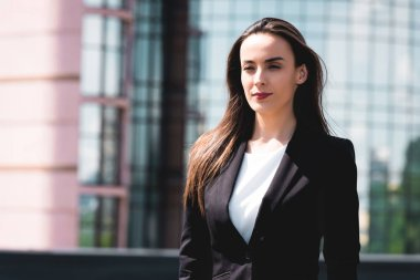 positive, confident businesswoman standing on rooftop and looking away