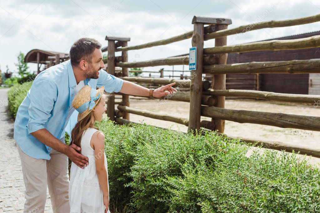 happy man pointing with finger near daughter in straw hat and dress while standing in zoo