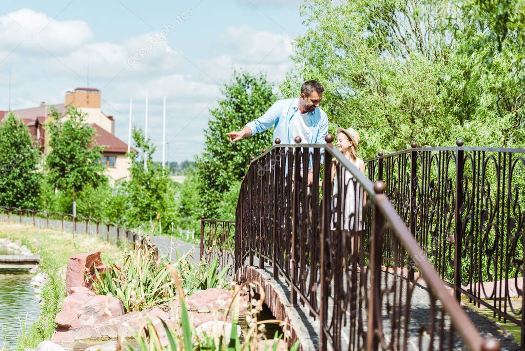selective focus of father pointing with finger near daughter while walking on bridge