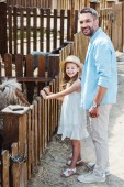 cheerful kid and man smiling while standing near pony in zoo