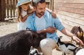 vidám ember megható kecske közelében aranyos lánya és vadkan az állatkert