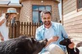 glücklicher bärtiger Vater berührt Ziege nahe niedlicher Tochter im Zoo