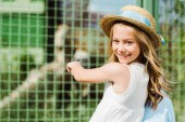 happy kid in straw hat looking at camera and gesturing near cage in zoo