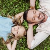 Nejlepší pohled na šťastného otce a roztomilou dceru, ležící na zelené trávě