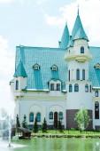 Luxusní hrad s modrou střechou poblíž stromů a fontány v létě