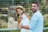 happy dad and daughter looking at camera near cage with wild animal in zoo