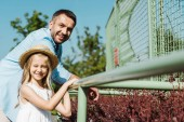 selective focus of cheerful kid in straw hat near happy dad standing in zoo