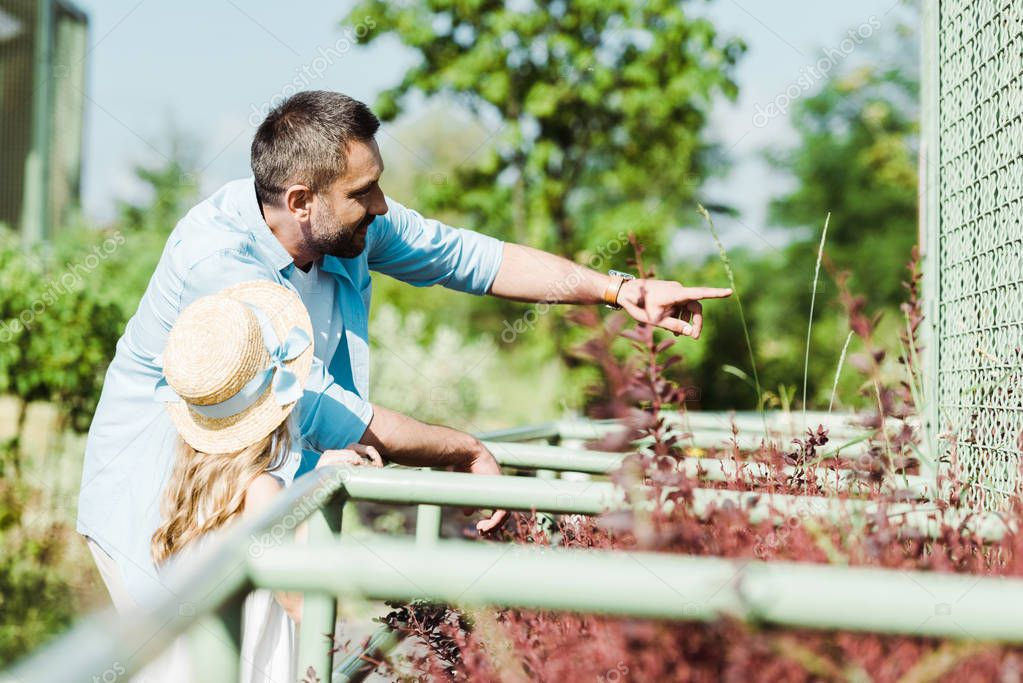 selective focus of father pointing with finger near kid and plants