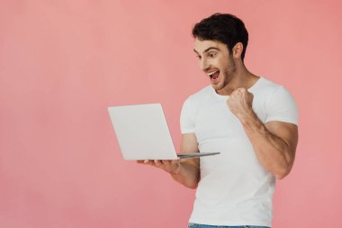 excited muscular man in white t-shirt using laptop and showing yes gesture isolated on pink
