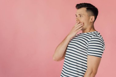 shocked young man in striped t-shirt covering mouth with hand isolated on pink