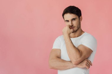 Serious pensive muscular man in white t-shirt looking at camera isolated on pink stock vector