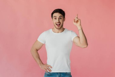 front view of excited muscular man in white t-shirt standing with hand on hip and showing idea sign isolated on pink