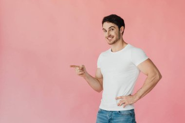 Smiling muscular man in white t-shirt standing with hand on hip and pointing with finger isolated on pink stock vector