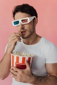 curious muscular man in 3d glasses eating popcorn isolated on pink