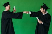 Fotografie two happy students in academic caps holding diplomas and touching fists isolated on green