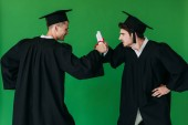 two students in academic caps holding diplomas and looking at each other isolated on green